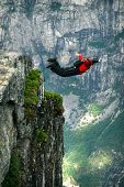 picture of cliffs  - Man jumping off a cliff with a parachute.