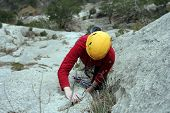 image of cave woman  - Man and woman climb over the wall in climbing shoes - JPG