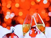 Champagne Flutes With Golden Bubbles On Red Christmas Lights Bokeh And Balls Decoration Background
