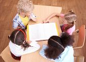stock photo of girl reading book  - Above view of pupils looking at page of encyclopaedia at reading lesson - JPG