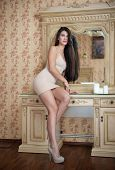 Charming young brunette woman in tight fit short nude dress in front of a mirror