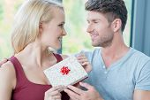 Loving man giving his wife a gift for Christmas  birthday  anniversary or Valentines Day as they smile into each others eyes
