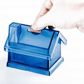 Blue House Money Box With Man Hand And Coin On White Background