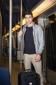Young Man Standing In Subway Train Going On Vacation
