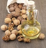 Walnut Oil And Walnuts On A Wooden Table.