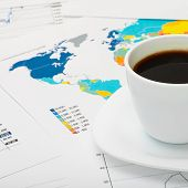 Coffee Cup Over World Map And Some Financial Documents