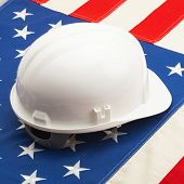 White Color Construction Helmet Laying Over Us Flag - Closeup Shoot