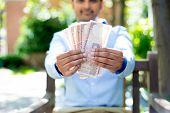 stock photo of gandhi  - Closeup portrait of banker executive ceo business man corporate employee holding rupees notes in front isolated outdoors outside background - JPG
