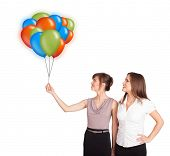 Beautiful young women holding colorful balloons