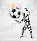 Funny man in full body suit holdig soccer ball