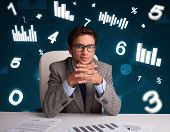 Young businessman sitting at desk with diagrams and statistics