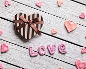 Word Love with heart shaped gift box on old white wooden plates. Sweet holiday background.