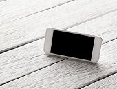 White smart phone with isolated screen on white wooden desk.