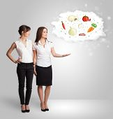 Pretty woman presenting a cloud of healthy nutritional vegetables concept