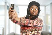 Black woman taking a selfie inside an office building