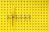 One Yellow Screwdriver Sits In A Rack On A Pegboard