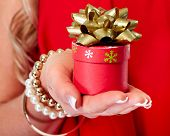 Hands of beautiful girl with Christmas gift.