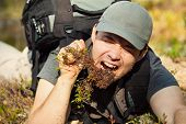 foto of survival  - Young hungry man tourist surviving by eating grass and roots in forest - JPG