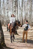 stock photo of brown horse  - romantic walk of bride and groom woman riding brown horse - JPG