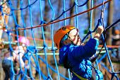 picture of safety  - little boy climbing in adventure activity park with helmet and safety equipment - JPG