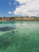 picture of school fish  - A large school of fish in the clear water of clean sea near the port of the island of La Digue and mountains in the distance Seychelles - JPG