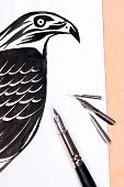 stock photo of fountains  - Fountain pen with drawing hawk on the wooden background - JPG