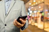 image of mall  - Handsome young man in shopping mall using mobile phone - JPG