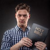 stock photo of holy-bible  - Young christian man showing showing with determination a Holy Bible  - JPG