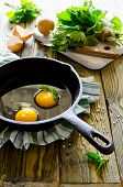 picture of scrambled eggs  - Scrambled eggs with nettles in a pan on a wooden table - JPG