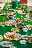 image of table manners  - Remaining plates leftover on the table with remaining Thai food - JPG