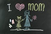 stock photo of mother-in-love  - Child drawing of I love mom picture using chalk on blackboard - JPG