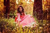 picture of cute kids  - cute curly kid girl in pink princess dress gathering dandelion flowers in summer forest - JPG