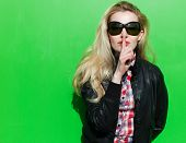 stock photo of silence  - Beautiful blond girl  summer sunny day in the black jacket and lips finger asking for silence - JPG
