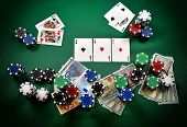 pic of ace spades  - Stack of chips three aces and money on green table - JPG