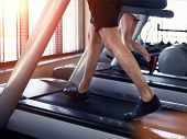 stock photo of treadmill  - Healthy man and woman running on a treadmill in a gym - JPG