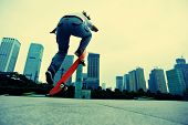 stock photo of skateboarding  - young skateboarder skateboarding ollie trick at city