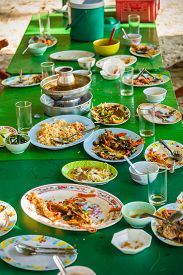 stock photo of table manners  - Remaining plates leftover on the table with remaining Thai food - JPG