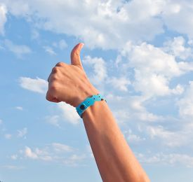 stock photo of all-inclusive  - hand with all inclusive bracelet over sky - JPG