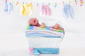 stock photo of apparel  - Newborn baby on a pile of clean dry towels - JPG