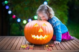stock photo of carving  - Little girl carving pumpkin at Halloween - JPG