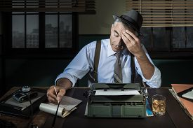 stock photo of 1950s style  - Professional reporter working late at night at his desk with vintage typewriter 1950s style - JPG