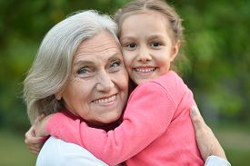 picture of grandmother  - Little cute girl with her grandmother in summer park - JPG