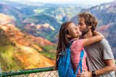 Couple in love kissing on nature travel hiking in Hawaii mountains. Young hikers people happy togeth poster