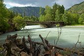 Mountain River And Old Wooden Bridge