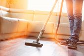 Low section of man cleaning hardwood floor with vacuum cleaner poster