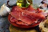closeup of an earthenware with some slices of spanish serrano ham on a wooden chopping board, and so poster