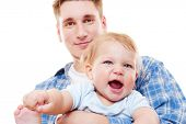 smiley man holding laughing baby boy over white background