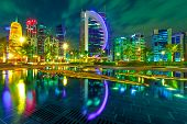 Doha West Bay High Rises Illuminated By Night Reflecting In Downtown Park. Colorful Glassed Skyscrap poster