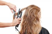 hairdresser straightening hair over white background
