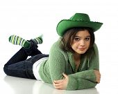 An attractive young teen wearing St. Patrick's Day garb, relaxed on the floor.  Isolated on white.